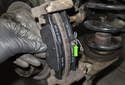 Install the new brake pads into the caliper and caliper-mounting bracket.