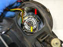 Remove the connector from the bulb (yellow arrow), push the retaining clip over the lugs (red arrow) and release the clip.