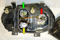 The low beam (red arrow) and fog light (yellow arrow) are replaced the same way as the high beam bulb; the turn signal bulb (green arrow) is replaced by removing the connector and turning the plastic base a quarter turn and pulling it from the housing.