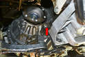 Loosen and remove the 18mm bolt on the right side of the transmission case by the flange (red arrow).