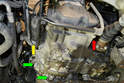 Remove the 16mm bolt holding the power steering cooling line to the transmission case (red arrow).