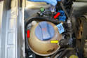 Remove the coolant reservoir by disconnecting the electrical connection (yellow arrow) and removing the two Philips head screws (red arrows).