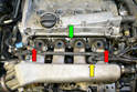 Next, remove the two 10mm nuts (red arrows) and eight 10mm bolts (green arrow) that hold the manifold to the engine.