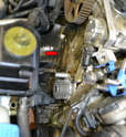 Clean the engine block of any dirt, debris or oil before installing the new tensioner (red arrow).