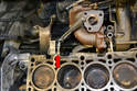 Remove the lower coolant line from the engine block (red arrow).
