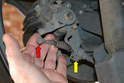 Cable Replacement - Next remove the other ball end (red arrow) from the tensioner arm and the circlip from the mounting bracket (yellow arrow).