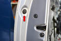 Begin by opening the door and using your trim tool to remove the grommet along the inside section of the door (red arrow).