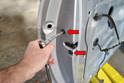 After removing the exterior door handle and the cable attached to it remove the two bolts holding the lock assembly to the door (red arrows).