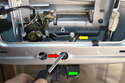 If you are working from inside the rear hatch with the panels removed insert a screwdriver into the access hole (red arrow) and place it behind the latch arm.