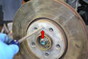 Remove the single Philips head screw holding the rotor or disk to the hub (red arrow).