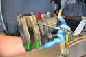 With the caliper off you can see the two brake pads (green arrows) along with the one brake wear sensor (yellow arrow).