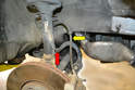 Leave the brake line attached to the caliper and hard line but remove the rubber flexible line (yellow arrow) from the holder on the strut (red arrow).