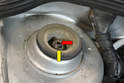 There is a 21mm nut (yellow arrow) around the top of the strut piston.