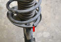 The base of the strut has a special place in the perch the spring needs to sit (red arrow).