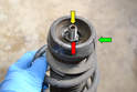 On the top of the strut is a suspension mounting bushing (green arrow) and another 21mm nut.