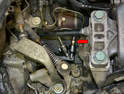 Located to the right of the transmission mount and behind and below the linkage is the clutch slave cylinder.