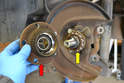 The old hub and bearing (red arrow) will probably be destroyed while pulling it off.