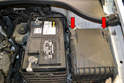 To remove the fuse and relay cover, slide the two clips (red arrows) towards the front of the car and pull the cover up and off.