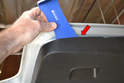 Insert your trim removal tool between the panel and hatch (red arrow).