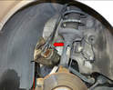 Hang the caliper out of the way with a bungee cord or rope (red arrow).