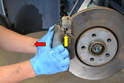 Pull the caliper back off the rotor (red arrow).
