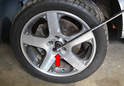 If you do not have an impact gun you can remove the center cap on the front wheel, leave the car on the ground and insert the 27mm socket through the center (red arrow).