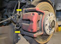 The caliper parking brake assembly is attached to the caliper mount by two 13mm bolts attached to two 15mm guide bolts (yellow arrows).