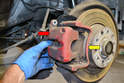 Pull the caliper (red arrow) off from its mount leaving the brake pads (yellow arrow).