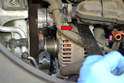 Use a pry bar and gently wiggle and pry the alternator from the mount (red arrow).