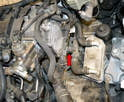 This photo illustrates the coolant temperature sensor on the left side of the engine (red arrow).