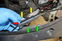 Unclip the two clips (yellow arrows) that hold the Bowden cable connection (red arrow) to the cross member above the left headlight (green arrows).
