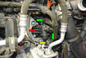 This photo illustrates the thermostat that is included in the thermostat housing (red arrow) along with the two coolant hoses (green arrows) and the lower radiator hose quick release connection (yellow arrow).