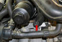 Working from below remove the T30 screw holding the charged air pipe bracket to the engine (red arrow).
