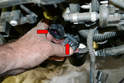 With the throttle body removed disconnect the plug for the injectors (red arrows).
