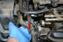 Disconnect the coolant hose from the top of the turbo where it joins the hard line by the tensioner (red arrow).
