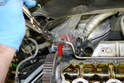 Label and disconnect the hose from the coolant reservoir to the metal coolant tube (red arrow).