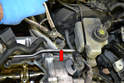 Label and disconnect the coolant hose at the junction in the metal line (red arrow).