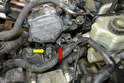 Remove the connection from the temperature sensor (yellow arrow) and the ground wire from the support bracket (red arrow).