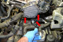 Remove the three T30 Torx screws for the coolant connection pipe (red arrows) and gently pull the pipe from the head.