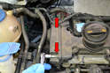 Remove the two T30 Torx screws on the top of the guard on the opposite end of the cylinder head from the pump (red arrows) that screw into the valve cover.