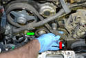 Remove the timing belt (red arrow) and the tensioner (green arrow).