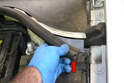 Pull the rubber trim piece that seals the plastic protective piece (red arrow).