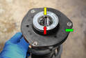 On the top of the strut is a suspension mounting bushing (green arrow) and a 21mm nut (red arrow).
