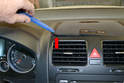 Gently pry the trim panel up from the top of the dash with your trusty plastic trim removal tool (red arrow).