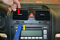 Gently pull the trim panel up while slipping your trim removal tool between the radio and the panel (yellow arrow).