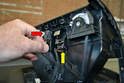 Separate the wiring connections for the air bag warning light (red arrow) and the emergency flashers (yellow arrow).