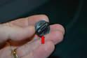 This photo illustrates one of the plastic retaining screws (red arrow).