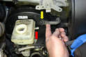 Remove the supply line for the clutch from the reservoir (red arrow, if your vehicle is so equipped).