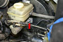 Use a deep socket 13mm and remove the two 13mm nuts holding the master cylinder to the booster (red arrow, one shown).