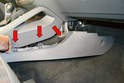 Using your trim removal tool gently push in towards the center console and unclip and lower the trim panel (red arrows).